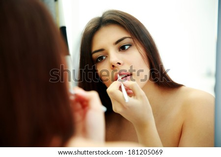 Young beautiful woman looking at mirror while doing makeup - stock photo
