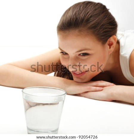 Young Beautiful woman looks at water glass - stock photo