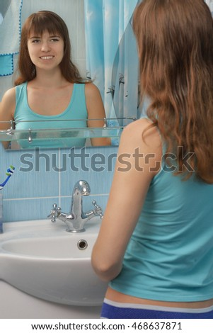 young beautiful woman looks in the mirror in the bathroom