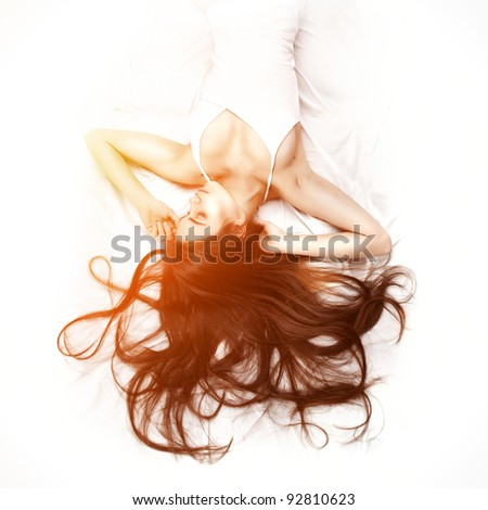 young beautiful woman lying down in bed and relaxing - stock photo