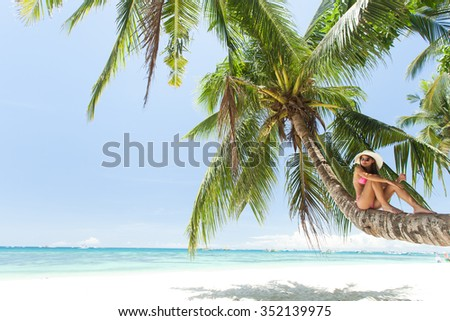 Young beautiful woman lying on a palm tree