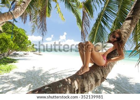 Young beautiful woman lying on a palm tree - stock photo