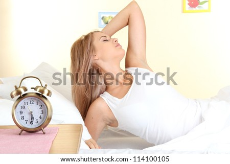 young beautiful woman lying on bed with alarm clock in bedroom - stock photo