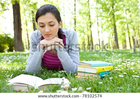 young beautiful woman lying on green field and reading book - stock photo