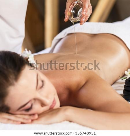 Young beautiful woman lying on massage table and enjoying massage - stock photo
