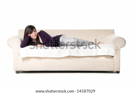 Young beautiful woman lying on sofa isolated on white background. - stock photo