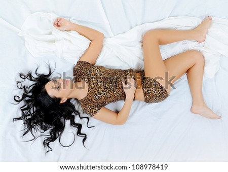 young beautiful woman lying on the bed. - stock photo