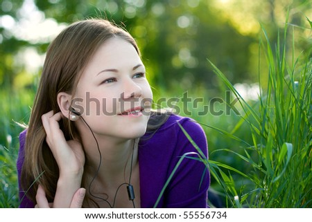 young beautiful woman lying on the grass and listening music - stock photo