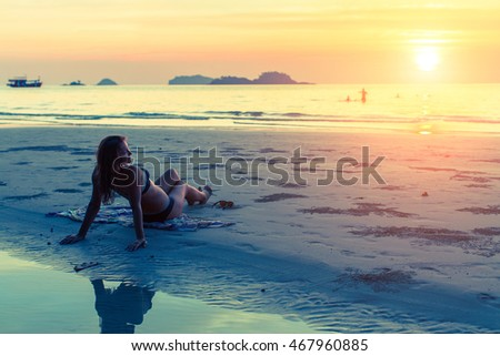 Young beautiful woman lying on the sea beach in the rays of the setting sun.