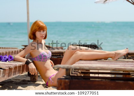 Young beautiful woman lying on wooden lounge by the sea - stock photo