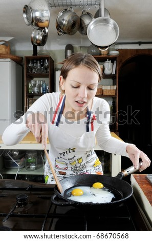 Young beautiful woman makes breakfast for her family