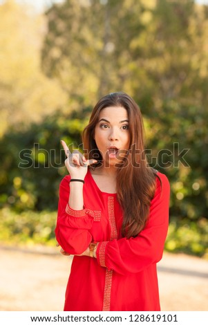 young beautiful woman makes funny face in red shirt - stock photo