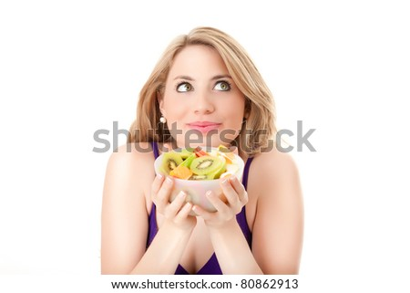 young beautiful woman makes funny face young beautiful woman with a fruit salad bowl isolated on white background - stock photo