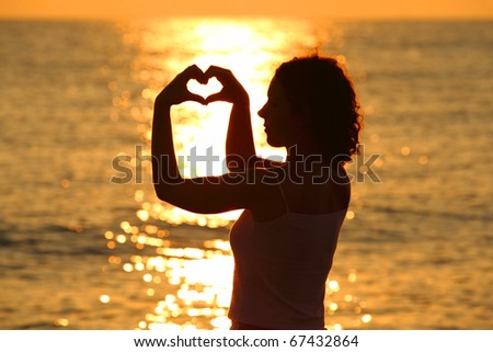 young beautiful woman makes heart by her hands at sunset, sea - stock photo