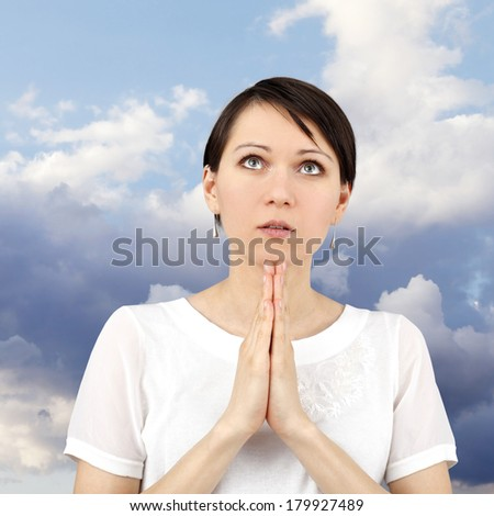 Young beautiful woman making a pray - stock photo