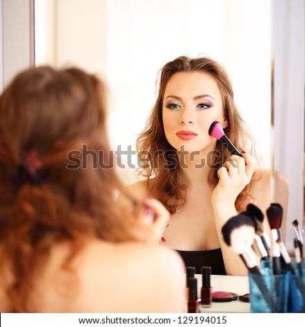 Young beautiful woman making make-up near mirror - stock photo