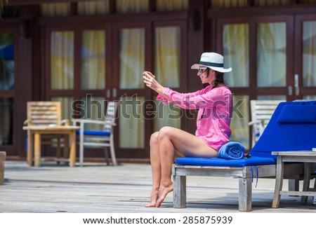 Young beautiful woman making selfie near swimming pool - stock photo