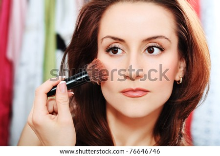 Young beautiful woman making up at home. - stock photo