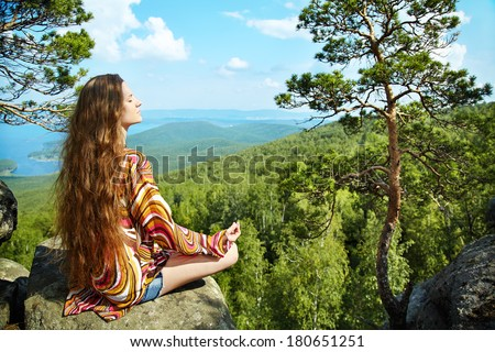 Young beautiful woman meditating at the mountains - stock photo