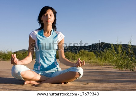 Young beautiful woman meditating. Copy space on right top. - stock photo