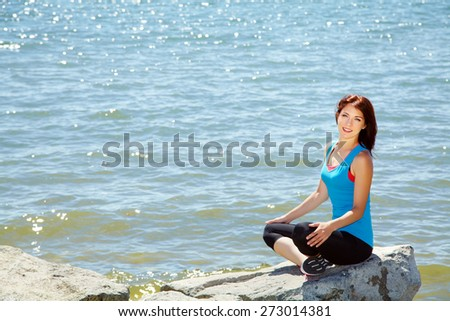 young beautiful woman meditating on the sea shore on a background of water. fitness, yoga outdoor - stock photo