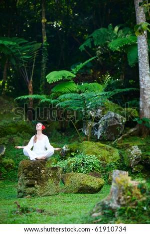 Young beautiful woman meditating outdoors at tranquil environment - stock photo