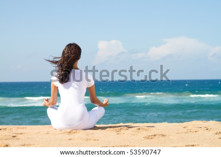 young beautiful woman meditation on beach - stock photo