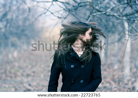 Young beautiful woman moving hair in a forest. - stock photo
