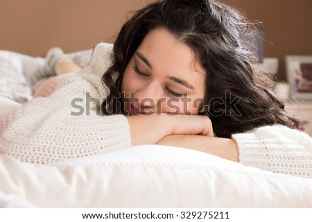 Young beautiful woman napping in bed - stock photo