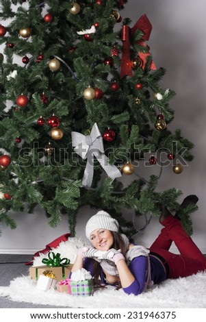 Young beautiful woman near new year tree with present - stock photo