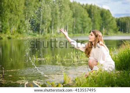 Young beautiful woman near water smiling - stock photo