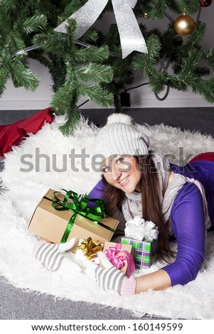Young beautiful woman near xmas tree with presents - stock photo
