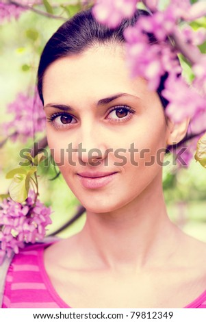 young beautiful woman next to blooming tree with violet flower, close up - stock photo
