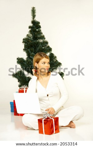 Young beautiful woman next to christmas tree, presents and laptop computer