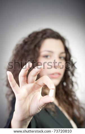 Young beautiful woman offers a pill - stock photo