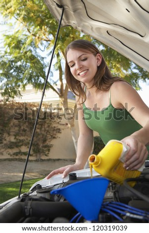 Young beautiful woman oiling engine of the car - stock photo