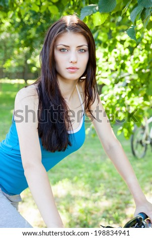 Young beautiful woman on a bicycle in the park in the morning - stock photo