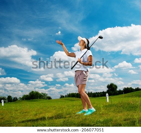 Young beautiful woman on a golf club field  - stock photo