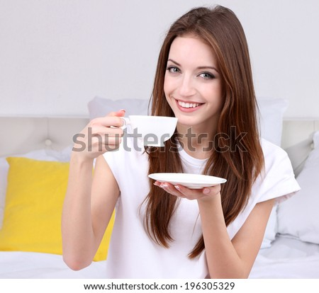 Young beautiful woman on bed with cup of coffee - stock photo