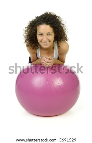 Young, beautiful woman on big pink ball. Smiling and looking at camera. Isolated on white in studio, front view