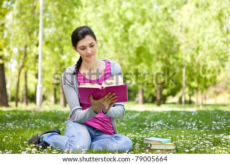 young beautiful woman  on green field and reading book - stock photo