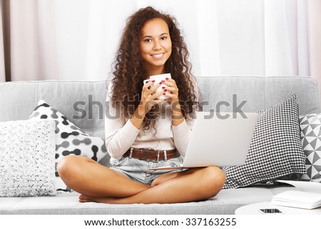 Young beautiful woman on sofa with laptop and drinking coffee on white background - stock photo