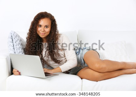 Young beautiful woman on sofa with laptop on white background - stock photo