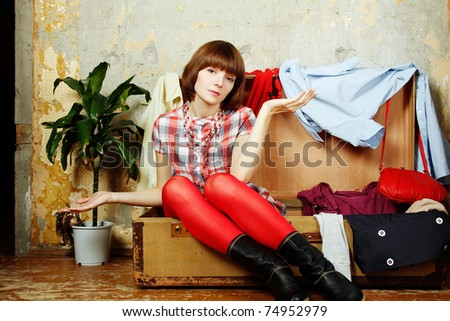 Young beautiful woman on the background of a concrete wall system sits in a big old-fashioned suitcase filled with clothes. - stock photo