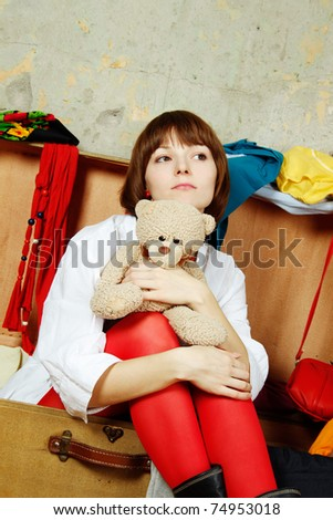 Young beautiful woman on the background of a concrete wall system sits in a big old-fashioned suitcase filled with clothes. Hugs a toy teddy - stock photo