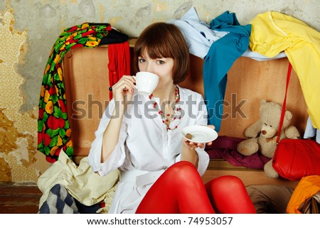 Young beautiful woman on the background of a concrete wall system sits in a big old-fashioned suitcase filled with clothes. Drinking coffee