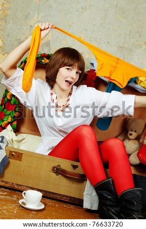 Young beautiful woman on the background of a concrete wall system sits in a big old-fashioned suitcase filled with clothes. Stretches tights - stock photo