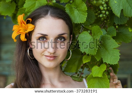 Young beautiful woman on the background of green grapes.