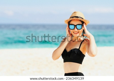 Young beautiful woman on the beach, Beautiful girl in sunglasses with hands near face on background of the sea and blue sky. (Color Process)