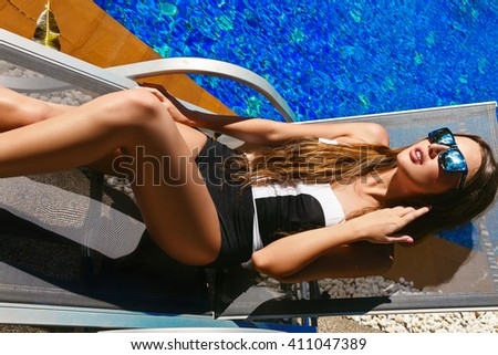 young beautiful woman on the beach on vacation. A girl in a swimsuit on the beach with a sports body. Girl sunbathing by the pool
